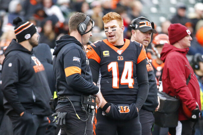 Cincinnati Bengals quarterback Andy Dalton (14) speaks with head coach Zac Taylor, center left, during the second half of an NFL football game against the New York Jets, Sunday, Dec. 1, 2019, in Cincinnati. (AP Photo/Frank Victores)