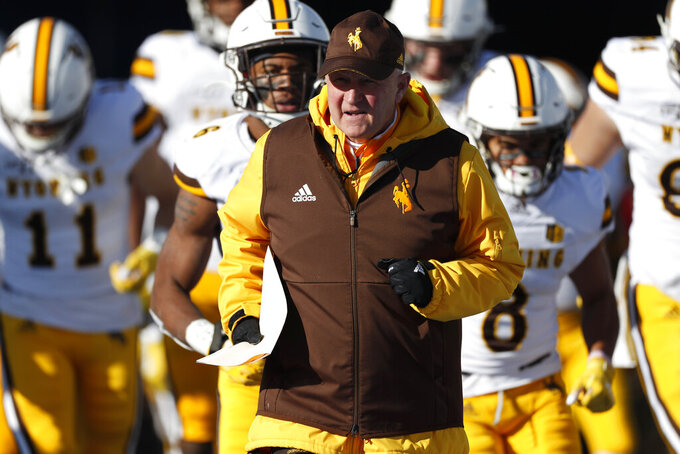 Wyoming head coach Craig Bohl leads his team on to the field for the second half of an NCAA college football game against Air Force Saturday, Nov. 30, 2019, at Air Force Academy, Colo. Air Force won 20-6. (AP Photo/David Zalubowski)