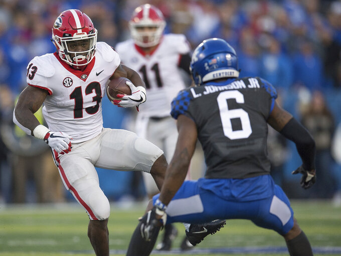 Georgia running back Elijah Holyfield (13) runs with the ball during the second half an NCAA college football game against Kentucky in Lexington, Ky., Saturday, Nov. 3, 2018. (AP Photo/Bryan Woolston)