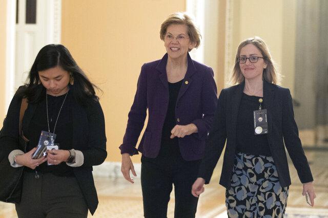Sen. Elizabeth Warren, D-Mass., center, walks to the Senate chamber for the impeachment trial of President Donald Trump at the Capitol, Thursday, Jan. 23, 2020, in Washington. (AP Photo/Steve Helber)