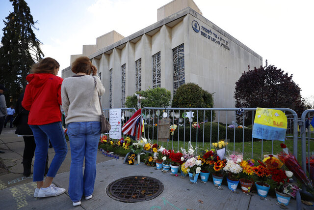 FILE - This Oct. 27, 2019 file photo shows passers by pausing outside the Tree of Life synagogue in Pittsburgh on the first anniversary of the shooting at the synagogue, that killed 11 worshippers. Nearly $5.5 million that poured in from donors after the 2018 attack is being distributed according to a plan outlined Monday by Jewish groups. (AP Photo/Gene J. Puskar, File)