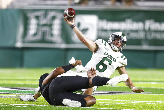 Portland State quarterback Davis Alexander (6) throws the ball away as he is taken down by a Hawaii defender during the second half of an NCAA college football game, Saturday, Sept. 4, 2021, in Honolulu. (AP Photo/Darryl Oumi)