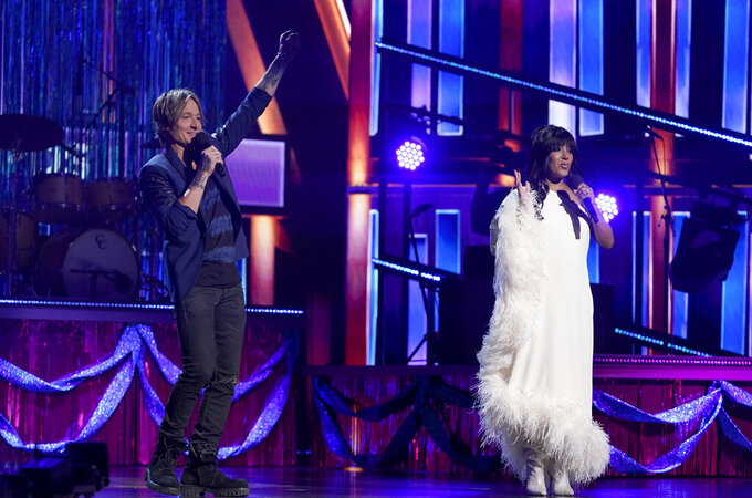 Hosts Keith Urban, left, and Mickey Guyton speak at the 56th annual Academy of Country Music Awards on Sunday, April 18, 2021, at the Grand Ole Opry in Nashville, Tenn. (AP Photo/Mark Humphrey)