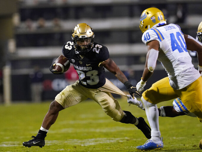 Colorado running back Jarek Broussard, left, is caught by his jersey by UCLA defensive back Stephan Blaylock, back right, as linebacker Caleb Johnson comes in to cover in the second half of an NCAA college football game Saturday, Nov. 7, 2020, in Boulder, Colo. (AP Photo/David Zalubowski)