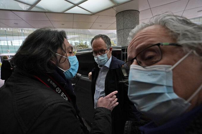 FILE - In this Wednesday, Feb. 10, 2021 file photo, Peter Ben Embarek, center, of a World Health Organization team is approached by a journalist as he arrives at the VIP terminal of the airport to leave, at the end of the WHO mission to investigate the origins of the coronavirus pandemic in Wuhan in central China's Hubei province. Peter Ben Embarek, the head of a World Health Organization team, working with Chinese colleagues to finish a long-awaited report into the origins of the coronavirus, said in interviews on Wednesday and Thursday that the team hopes the report will be ready for release next week.(AP Photo/Ng Han Guan, file)