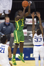 Oregon's Eugene Omoruyi scores against Seton Hall's Ike Obiagu, left, and Shavar Reynolds Jr. during the first half of an NCAA college basketball game in Omaha, Neb., Friday, Dec. 4, 2020. (AP Photo/Kayla Wolf)