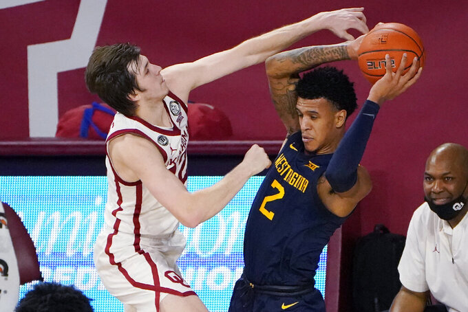 Oklahoma guard Austin Reaves, left, pressures West Virginia forward Jalen Bridges (2) in the first half of an NCAA college basketball game Saturday, Jan. 2, 2021, in Norman, Okla. (AP Photo/Sue Ogrocki)
