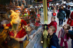 FILE - Garrett Folts, 7, left, looks at a Macy's Santa Claus window display with his brother Cameron, 9, center and sister Chloe, 5, while shopping with their mother, Nov. 21, 2007 in New York. Macy's said Santa Claus won't be greeting kids at its flagship New York store this year due to the coronavirus, interrupting a holiday tradition started nearly 160 years ago. However, Macy's said the jolly old man will still appear at the end of the televised Macy's Thanksgiving Day parade. (AP Photo/Mark Lennihan, File)