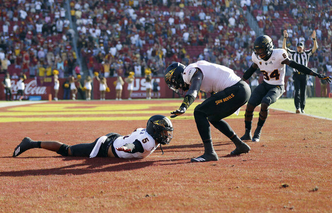 Arizona State quarterback Manny Wilkins, bottom, left, celebrates with teammates in the end zone after his rushing touchdown against Southern California during the second half of an NCAA college football game Saturday, Oct. 27, 2018, in Los Angeles. (AP Photo/Marcio Jose Sanchez)