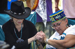 """Actress and activist Jane Fonda, left, locks hands with Grandmother Mary Lyons after they prepared to perform a traditional water ceremony, on Monday, June 7, 2021, in Clearwater County, Minn. More than 2,000 Indigenous leaders and """"water protectors"""" gathered in Clearwater County from around the country to protest the construction of Enbridge Line 3. The day started with a prayer circle and moved on to a march to the Mississippi headwaters where the oil pipeline is proposed to be built. (Alex Kormann/Star Tribune via AP)"""