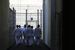 In this photo taken Sept. 10, 2019, detainees walk toward a fenced recreation area at the GEO Group's immigration jail in Tacoma, Wash., during a media tour. After nearly four years of litigation and pandemic-related delays, a federal jury on Tuesday, June 15, 2021, began deliberating whether the GEO Group must pay minimum wage to detainees who perform cooking, cleaning and other tasks at the facility – instead of the $1 per day they typically receive. (AP Photo/Ted S. Warren)