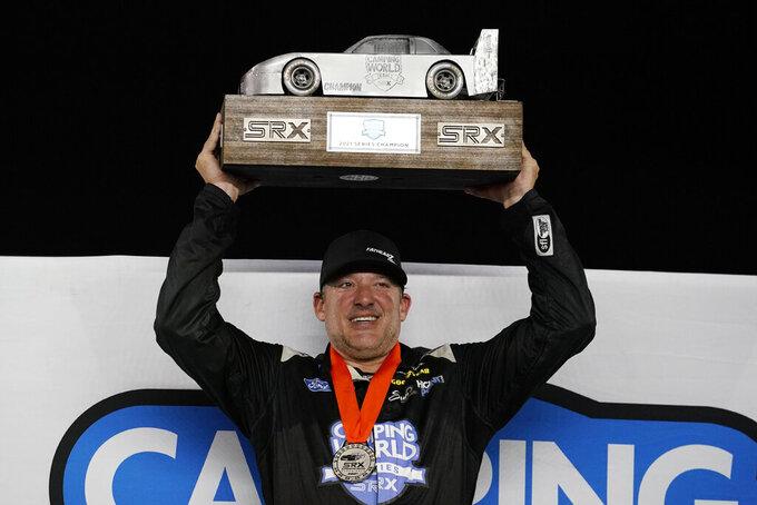 Tony Stewart holds the SRX 2021 Series championship trophy after the SRX Series auto race Saturday, July 17, 2021, in Nashville, Tenn. (AP Photo/Mark Humphrey)