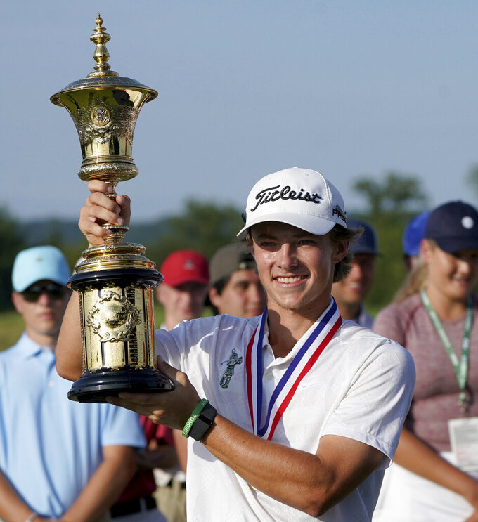 James Piot lifts the trophy after defeating Austin Greaser on the 17th hole to win the U.S. Amateur Championship golf tournament Sunday, Aug. 15, 2021, at Oakmont Country Club in Oakmont, Pa. (Matt Freed/Pittsburgh Post-Gazette via AP)