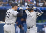 New York Yankees' Gleyber Torres, right, is met by teammate Luke Voit after hitting a two run home run against the Toronto Blue Jays in the sixth inning of a baseball game in Toronto, Saturday, Sept. 14, 2019. (Fred Thornhill/The Canadian Press via AP)