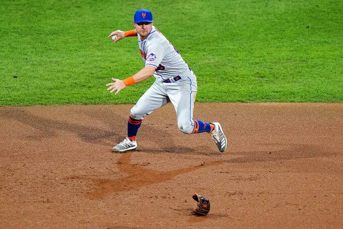 New York Mets third baseman J.D. Davis throws to first after losing his glove while fielding a single by Philadelphia Phillies' Alec Bohm during the fifth inning of a baseball game, Tuesday, Sept. 15, 2020, in Philadelphia. (AP Photo/Matt Slocum)