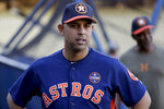FILE - In this Oct. 23, 2017, file photo, Houston Astros bench coach Alex Cora watches batting practice during media day for baseball's World Series against the Los Angeles Dodgers, in Los Angeles. Houston  manager AJ Hinch and general manager Jeff Luhnow were suspended for the entire season Monday, Jan. 13, 2020,  and the team was fined $5 million for sign-stealing by the team in 2017 and 2018 season. Commissioner Rob Manfred announced the discipline and strongly hinted that current Boston manager Alex Cora — the Astros bench coach in 2017 — will face punishment later. Manfred said Cora developed the sign-stealing system used by the Astros. (AP Photo/David J. Phillip, File)