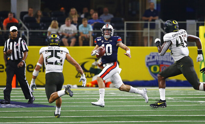 Auburn quarterback Bo Nix (10) looks to pass as Oregon safety Brady Breeze (25) and Oregon defensive end Gus Cumberlander (45) pursue during the first half of an NCAA college football game, Saturday, Aug. 31, 2019, in Arlington, Texas. (AP Photo/Ron Jenkins)