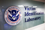 A sign to the Victim Identification Lab, part of Homeland Security's Child Exploitation Investigations Unit, is seen in Fairfax, Va., Friday, Nov. 22, 2019. The Homeland Security Investigations section's  little-known Child Exploitation Investigations lab is where agents scour disturbing photos and videos of child sexual abuse.  They look for unlikely clues that help them identify the children and bring their abusers to justice. In one case, it was the loud, persistent chirping of a bird. Another time, it was unusual playground equipment.   (AP Photo/Jacquelyn Martin)