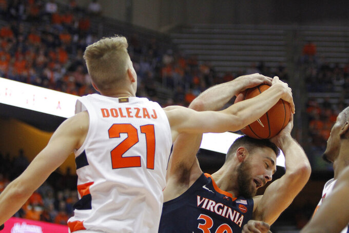 Syracuse's Marek Dolezaj, left, and Virginia's Jay Huff, right, battle for a rebound during the first half of an NCAA college basketball game in Syracuse, N.Y., Wednesday, Nov. 6, 2019. (AP Photo/Nick Lisi)