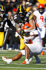 Illinois running back Reggie Corbin (2) is tackled by Iowa defensive end A.J. Epenesa (94) during the first half of an NCAA college football game, Saturday, Nov. 23, 2019, in Iowa City, Iowa. (AP Photo/Charlie Neibergall)