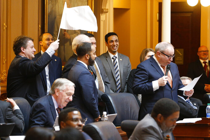 FILE - In this Friday Feb. 28, 2020, file photo, Del. Alfonzo Lopez, D-Arlington, left, waves a white flag as Del. Mark Sickles, D-Fairfax, explains another bill during the House session at the Capitol in Richmond, Va. Democrats who have transformed Virginia at whiplash speed over the past two years will be defending their full control of the statehouse in fall 2021. (AP Photo/Steve Helber, File)