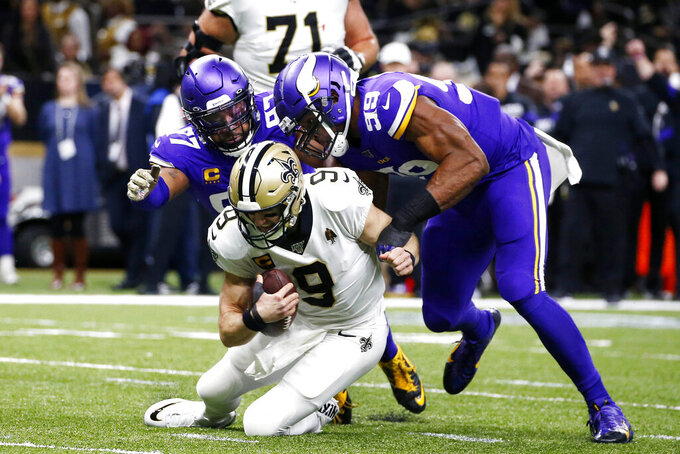 New Orleans Saints quarterback Drew Brees (9) is sacked by Minnesota Vikings defensive end Danielle Hunter (99) and defensive end Everson Griffen (97) in the first half of an NFL wild-card playoff football game, Sunday, Jan. 5, 2020, in New Orleans. (AP Photo/Butch Dill)