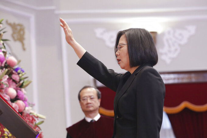 In this photo released by the Taiwan Presidential Office, Taiwanese President Tsai Ing-wen raises her hand during an inauguration ceremony at the Presidential office in Taipei, Taiwan Wednesday, May 20, 2020. President Tsai been inaugurated for a second term amid increasing pressure from China on the self-governing island democracy it claims as its own territory. (Taiwan Presidential Office via AP)