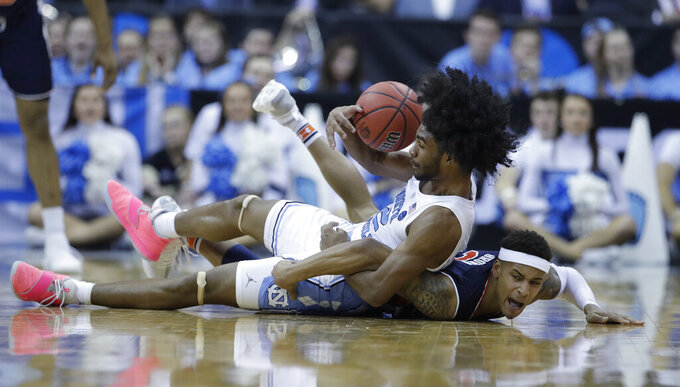 North Carolina's Coby White, left, and Auburn's Bryce Brown dive after a loose ball during the second half of a men's NCAA tournament college basketball Midwest Regional semifinal game Friday, March 29, 2019, in Kansas City, Mo. (AP Photo/Charlie Riedel)
