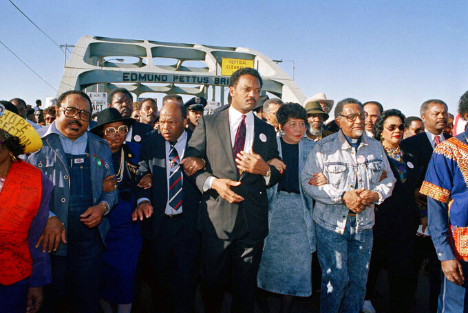 """FILE - In this March 4, 1990, file photo, civil rights figures lead marchers across the Edmund Pettus Bridge during the recreation of the 1965 Selma to Montgomery march in Selma, Ala. From left are Hosea Williams of Atlanta, Georgia Congressman John Lewis, the Rev. Jesse Jackson, Evelyn Lowery, SCLC President Joseph Lowery and Coretta Scott King. This Sunday, March 7, 2021, marks the 56th anniversary of those marches and """"Bloody Sunday,"""" when more than 500 demonstrators gathered on March 7, 1965, to demand the right to vote and cross Selma's Edmund Pettus Bridge. They were met by dozens of state troopers and many were severely beaten. (AP Photo/Jamie Sturtevant, File)"""
