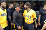 Pittsburgh Pirates pitching coach Ray Searage, left center, and starting pitcher Trevor Williams (34) share a moment together after the final baseball game of the Pirates season, a 3-1 loss to the Cincinnati Reds, in Pittsburgh, Sunday, Sept. 29, 2019. (AP Photo/Gene J. Puskar)