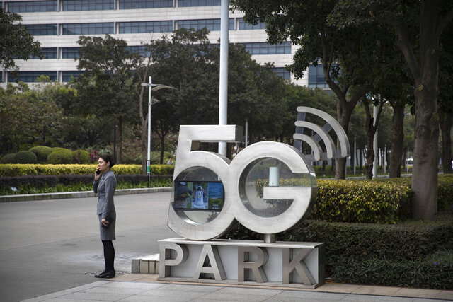 A Huawei employee talks on her cellphone as she stands next to a sign at Huawei's campus in Shenzhen in southern China's Guandong Province, Thursday, Dec. 5, 2019. Chinese tech giant Huawei is asking a U.S. federal court to throw out a rule that bars rural phone carriers from using government money to purchase its equipment on security grounds. (AP Photo/Mark Schiefelbein)