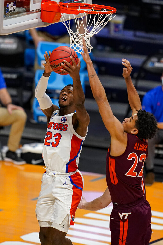 Florida guard Scottie Lewis (23) shoots in front of Virginia Tech forward Keve Aluma (22) in the second half of a first round game in the NCAA men's college basketball tournament at Hinkle Fieldhouse in Indianapolis, Friday, March 19, 2021. (AP Photo/Michael Conroy)