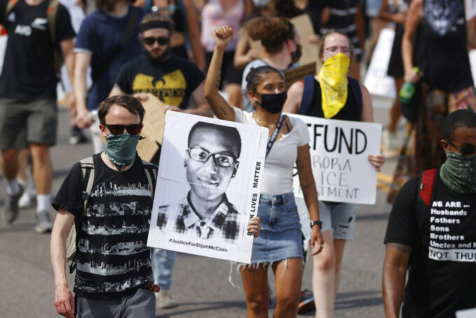 FILE - In this June 27, 2020 file photo, demonstrators carry placards as they walk down Sable Boulevard during a rally and march over the death of Elijah McClain in Aurora, Colo. Colorado police reform advocates say the recent indictments of three suburban Denver police officers and two paramedics on manslaughter and other charges in the death of Elijah McClain could be a pivotal step toward meaningful accountability. (AP Photo/David Zalubowski, File)
