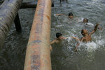 FILE - In this Aug. 4, 2008 file photo, children play under oil pipes that cross a river in the province of Sucumbios, Ecuador.  Late Tuesday, July 10, 2018, Ecuador's highest court upheld a $9.5 billion judgment against oil giant Chevron for decades of rainforest damage that harmed indigenous people. (AP Photo/Dolores Ochoa, File)