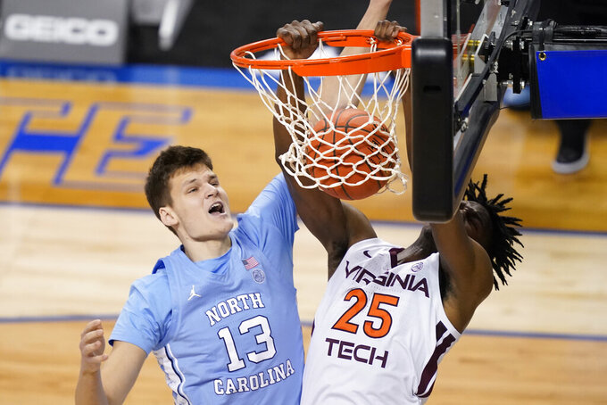 Virginia Tech forward Justyn Mutts (25) dunks the ball in front of North Carolina forward Walker Kessler (13) during the first half of an NCAA college basketball game in the quarterfinal round of the Atlantic Coast Conference tournament in Greensboro, N.C., Thursday, March 11, 2021. (AP Photo/Gerry Broome)
