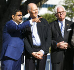 FILE - In this March 23, 2018 file photo, developer Danny Gaekwad, left, points in the direction where his hotel will be built while talking with Florida Governor Rick Scott, center, as Ocala Mayor Kent Guinn listens in downtown  Ocala, Fla.  Since the coronavirus crisis started, hotel owners say they are struggling to get relief on a type of loan that Wall Street investors buy.  [Doug Engle/Ocala Star-Banner via AP)