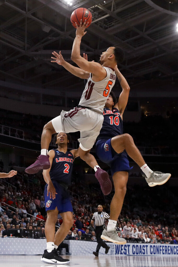 Virginia Tech guard Justin Robinson drives to the basket past Liberty guards Darius McGhee (2) and Elijah Cuffee (10) during the second half of a second-round game in the NCAA men's college basketball tournament Sunday, March 24, 2019, in San Jose, Calif. (AP Photo/Jeff Chiu)
