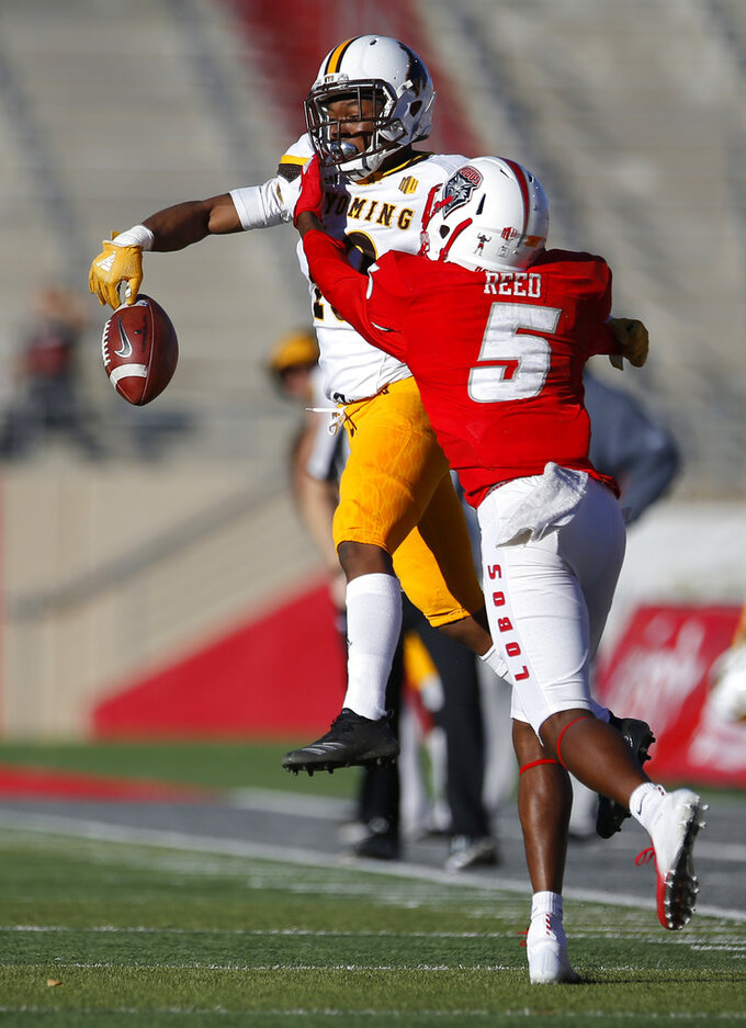 Wyoming cornerback Keyon Blakenbaker (18) breaks up a pass intended for New Mexico wide receiver Patrick Reed (5) during the second half of an NCAA college football game in Albuquerque, N.M., Saturday, Nov. 24, 2018. Wyoming won 31-3. (AP Photo/Andres Leighton)