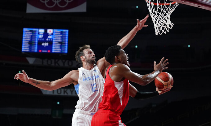 Japan's Rui Hachimura (8), right, drives to the basket over Argentina's Marcos Delia (12) during men's basketball preliminary round game at the 2020 Summer Olympics, Sunday, Aug. 1, 2021, in Saitama, Japan. (AP Photo/Charlie Neibergall)