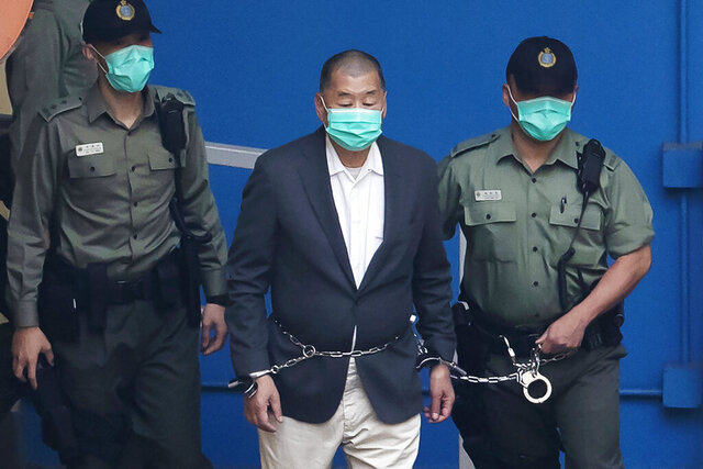FILE - In this Dec. 12, 2020, file photo, Jimmy Lai, center, who founded the Apple Daily tabloid, is escorted by Correctional Services officers to get on a prison van before appearing in a court, in Hong Kong. Hong Kong media tycoon Lai was granted bail on Wednesday, Dec. 23, nearly three weeks after he was remanded in custody over fraud and national security-related charges. (AP Photo/Kin Cheung, File)