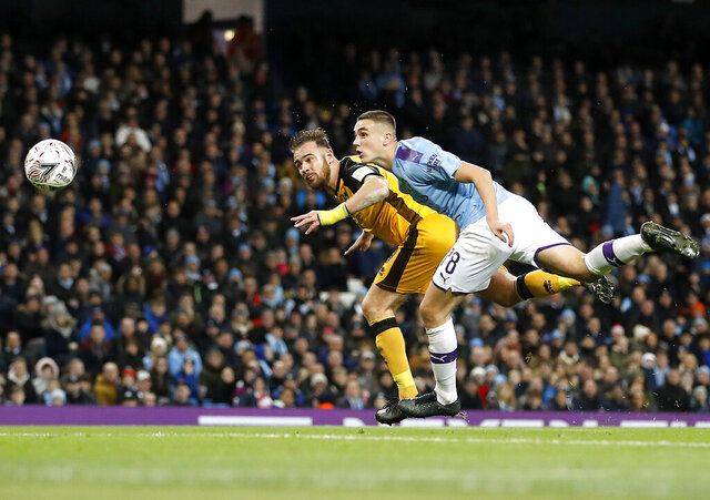 Port Vale's Tom Pope, left, scores his side's first goal of the game during the English FA Cup third round soccer match between Manchester City and Port Vale at the Etihad Stadium, Manchester, England, Saturday, Jan. 4, 2020. (Martin Rickett/PA via AP)