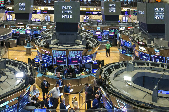 In this photo provided by the New York Stock Exchange, traders, foreground center,  gather at a post on the NYSE trading floor during the direct listing of Palantir Technologies, Wednesday, Sept. 30, 2020. Shares of data-mining company Palantir jumped 47% to $10.67 on their first day of trading. The company was born 17 years ago with the help of CIA seed money. Palantir isn't selling new shares to raise money. Instead, it's listing existing shares for public trading. (NYSE Photo/Courtney Crow via AP)
