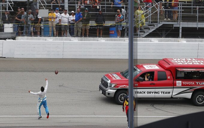 Bubba Wallace tosses a football into the stands during a rain delay at the NASCAR cup series auto race at Michigan International Speedway, Sunday, June 9, 2019, in Brooklyn, Mich. The race has been rescheduled for Monday. (AP Photo/Carlos Osorio)
