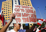 A student protester holds a placard as he protests against the government in front of the education ministry in Beirut, Lebanon, Friday, Nov. 8, 2019. Lebanese protesters are rallying outside state institutions and ministries to keep up the pressure on officials to form a new government to deal with the country's economic crisis. (AP Photo/Hussein Malla)