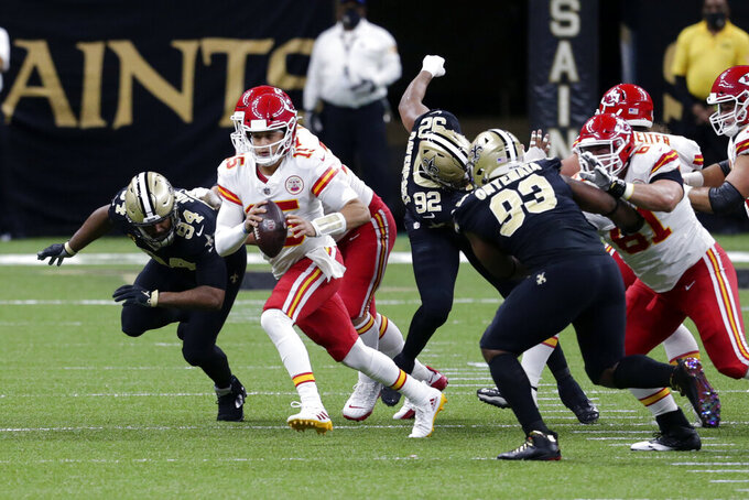 Kansas City Chiefs quarterback Patrick Mahomes (15) scrambles under pressure from New Orleans Saints defensive end Cameron Jordan (94), defensive tackle David Onyemata (93) and defensive end Marcus Davenport (92) in the first half of an NFL football game in New Orleans, Sunday, Dec. 20, 2020. (AP Photo/Butch Dill)