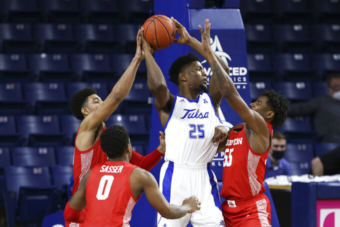 Houston's Caleb Mills, left, Marcus Sasser (0) and Brison Gresham defend against Tulsa's Rey Idowu during the second half of an NCAA college basketball game in Tulsa, Okla., Tuesday, Dec. 29, 2020. Tulsa won 65-64. (AP Photo/Dave Crenshaw)