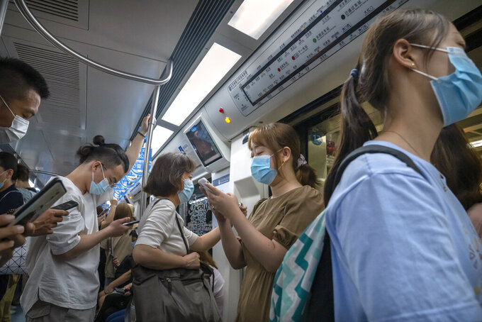 People wearing face masks to protect against COVID-19 ride on a subway train during the morning rush hour in Beijing, Wednesday, Aug. 4, 2021. The coronavirus's delta variant is challenging China's costly strategy of isolating cities, prompting warnings that Chinese leaders who were confident they could keep the virus out of the country need a less disruptive approach. (AP Photo/Mark Schiefelbein)