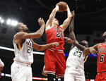 Chicago Bulls forward Lauri Markkanen (24) grabs a rebound as Utah Jazz center Rudy Gobert (27) and forward Royce O'Neale (23) defend him during the first half of an NBA basketball game Saturday, March 23, 2019, in Chicago. (AP Photo/David Banks)