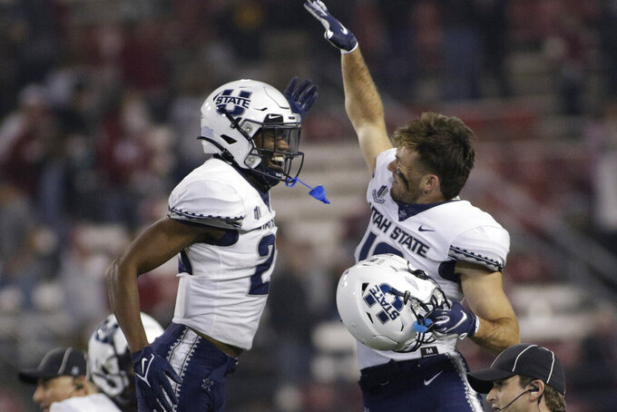 Utah State safety Dominic Tatum, left, and wide receiver Brandon Bowling celebrate the team's 26-23 win against Washington State in an NCAA college football game, Saturday, Sept. 4, 2021, in Pullman, Wash. (AP Photo/Young Kwak)