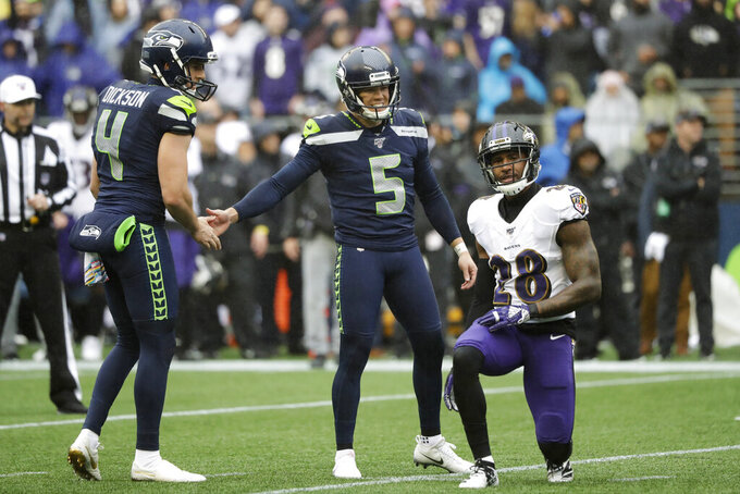 Seattle Seahawks kicker Jason Myers (5) shakes hands with holder Michael Dickson (4) as Baltimore Ravens' Justin Bethel (28) looks on after Myers made a field goal during the first half of an NFL football game, Sunday, Oct. 20, 2019, in Seattle. (AP Photo/Elaine Thompson)